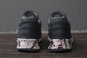 Sportowe buty new balance pomalowane na szaro, z efektem splash na podeszwie.